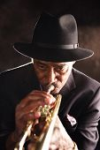 stock photo of katrina  - an elderly black man in an emotive setting playing his trumpet - JPG