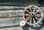 pic of wagon wheel  - Large wooden wagon wheel in the background of the log walls - JPG