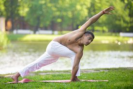 picture of revolver  - Profile of attractive Indian young man in white linen clothes practicing yoga fitness pilates on river bank in park standing in Revolved Side Angle Pose Parivrtta Parsvakonasana full length - JPG