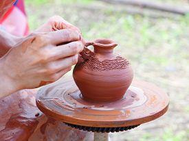 stock photo of loamy  - Potter makes on pottery wheel clay pot - JPG