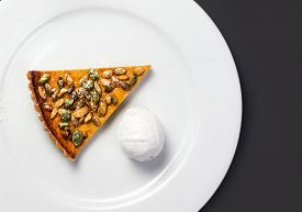 stock photo of pumpkin pie  - Pumpkin Pie with whipped cream and pumpkin seeds on white plate over black chalk board - JPG