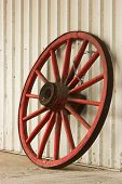 stock photo of ox wagon  - Red antique wagon wheel leaning against a steel shed - JPG