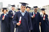 education, graduation and people concept - group of happy international students in mortar boards an poster