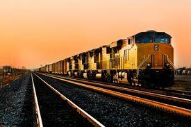 picture of chug  - Cargo locomotive railroad engine crossing Arizona desert wilderness during sunset - JPG