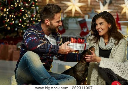 poster of Christmas couple at home in Winter. Happy young couple sitting on floor at home with dog and gift bo