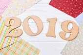 Wooden Number 2019 On Wooden Background. Carved Wooden Digit 2019 And Colored Patterned Craft Paper  poster