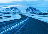 Road to the snow-capped mountains at twilight in winter.     The Ring Road  (Route 1) of Iceland, b poster