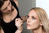 makeup styl?st apply?ng makeup on the model closeup beauty face poster