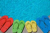 pic of swimming pool family  - Colored flipflops of a family of four by the swimming pool - JPG