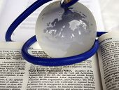 pic of world health organization  - Glass globe of the earth lying with a blue stethoscope draped around the globe on a medical dictionary open at the World Health Organization page - JPG