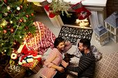 Christmas couple at home in Winter. Happy young couple lying on floor at home with dog at Christmas  poster