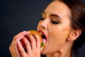 Hamburger eating contest. Woman eat with appetite fast food. Girl eats after long diet. poster