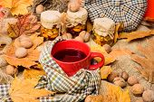 Cozy Autumnal Atmosphere. Warming Beverage Concept. Mug Of Tea Surrounded By Scarf Red Background Wi poster