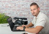 A Man Video Editor With Laptop And Professional Video Camera poster