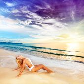foto of tropical island  - Woman sunbathing on the beach at sunrise time - JPG