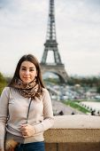 Beautiful Lady Sist On Border Against Of Eiffel Tower. Lady Smile And Have Fun poster