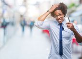 Afro american man holding credit card over isolated background stressed with hand on head, shocked w poster