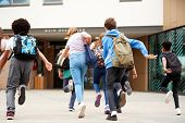 Group Of High School Students Running Into School Building At Beginning Of Class poster