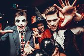 Young People In Costumes Celebrating Halloween. Group Of Young Happy Friends Wearing Halloween Costu poster