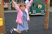 picture of sock-monkey  - smiling girl hanging from monkey bars on school playground  - JPG