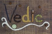 picture of vedic  - The word Vedic spelled out in a decorative way with spices and seeds used in the ayurveda diet and healing on a wooden countertop surface - JPG