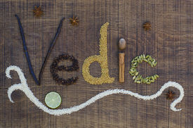 stock photo of vedic  - The word Vedic spelled out in a decorative way with spices and seeds used in the ayurveda diet and healing on a wooden countertop surface - JPG