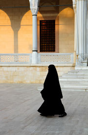 stock photo of burka  - Muslim woman in black burka walking at the front of the Mosque entrance right before sunset  in Adana - JPG