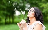 picture of dandelion  - adult beautiful woman blowing a dandelion - JPG