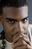 stock photo of praying hands  - Young black male with hands clutched in front of face as if to pray - JPG
