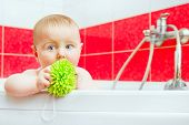 cute smiling baby in bath with green wisp