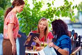 stock photo of politeness  - polite waitress serving clients on summer cafe terrace - JPG