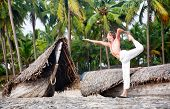 picture of natarajasana  - Yoga natarajasana dancer pose by fit man in white trousers on the beach near the fishermen boats in Varkala Kerala India - JPG