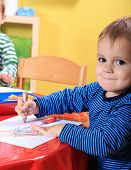 foto of crotch  - Cute caucasian toddler drawing a picture in kindergarten - JPG