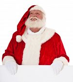 Santa Claus standing behind blank sign looking up. All on white background.