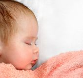 newborn baby sleeping under peachey blanket