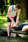stock photo of mans-best-friend  - Man gives massage of calf to his friend after sport training outdoor