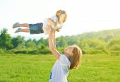 pic of throw up  - happy family. Mother throws up baby in the sky in nature ** Note: Shallow depth of field - JPG