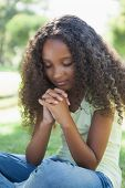 stock photo of pentecostal  - Young girl praying in the park on a sunny day - JPG