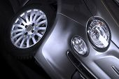 picture of alloy  - Detail of the front headlight parking light and tyre of a silver car with a spoked alloy sports wheel close up low angle - JPG