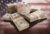 image of money prize  - Thousands of Dollars and Piggy Bank with Reflection of American Flag on Table - JPG