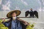 picture of fisherman  - Cormorant fisherman and his bird on the Li River in Yangshuo - JPG