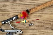 stock photo of fishing bobber  - Horizontal top view photo of fishing lures bobbers sinkers cork pole handle and part of reel on faded wood - JPG