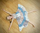 foto of stressless  - Little girl lying on the floor with legs and hands apart - JPG
