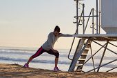 stock photo of early morning  - woman stretching leg muscle before early morning run workout on beach - JPG