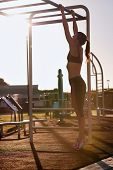 picture of pull up  - young athletic fitness woman working out at outdoor gym doing pull ups at sunrise - JPG