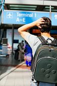 foto of confuse  - Confused young man with backpack looking for right direction in airport - JPG