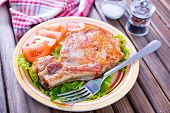 picture of shoulder-blade  - fried meat with salad on plate and on a table - JPG