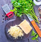 image of grating  - grated cheese on the wooden board and on a table - JPG