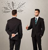 picture of backstabbers  - Ruthless businessman handshake with a hiding weapon and drawn curly lines around his head  - JPG