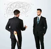 picture of backstabbers  - Ruthless businessman hiding a weapon and weaving plan around his head  - JPG